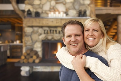 Happy Affectionate Couple at Rustic Fireplace in Log Cabin